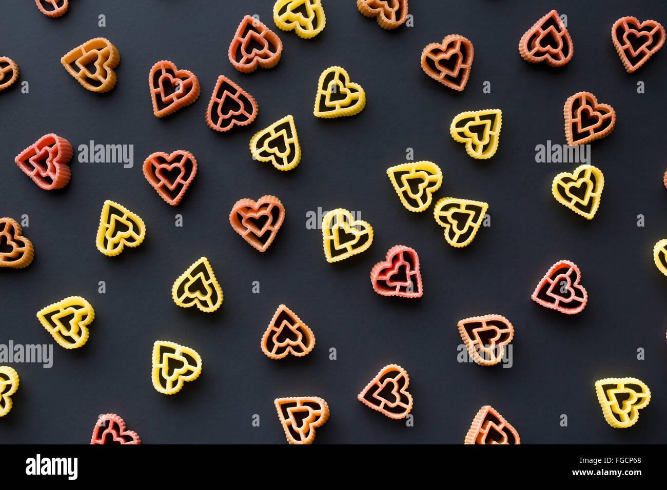 herzförmige Nudeln auf schwarzem Hintergrund Stockfoto