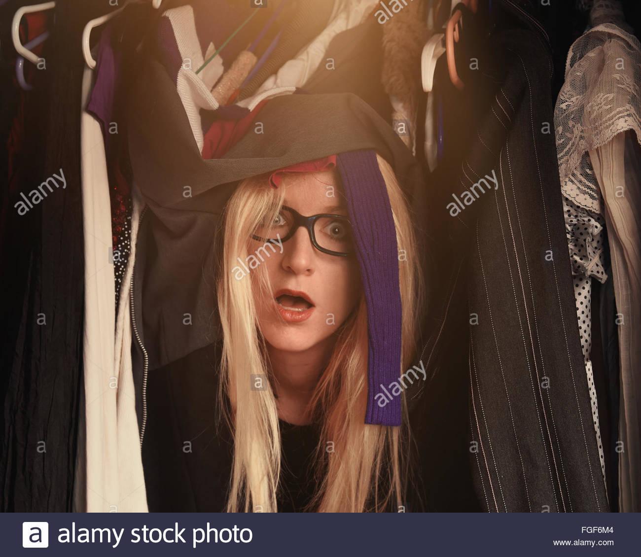 Eine Frau ist in einem Schrank unordentlich Kleidung mit Brille für einen Stil oder Mode Konzept überwältigt. Stockbild