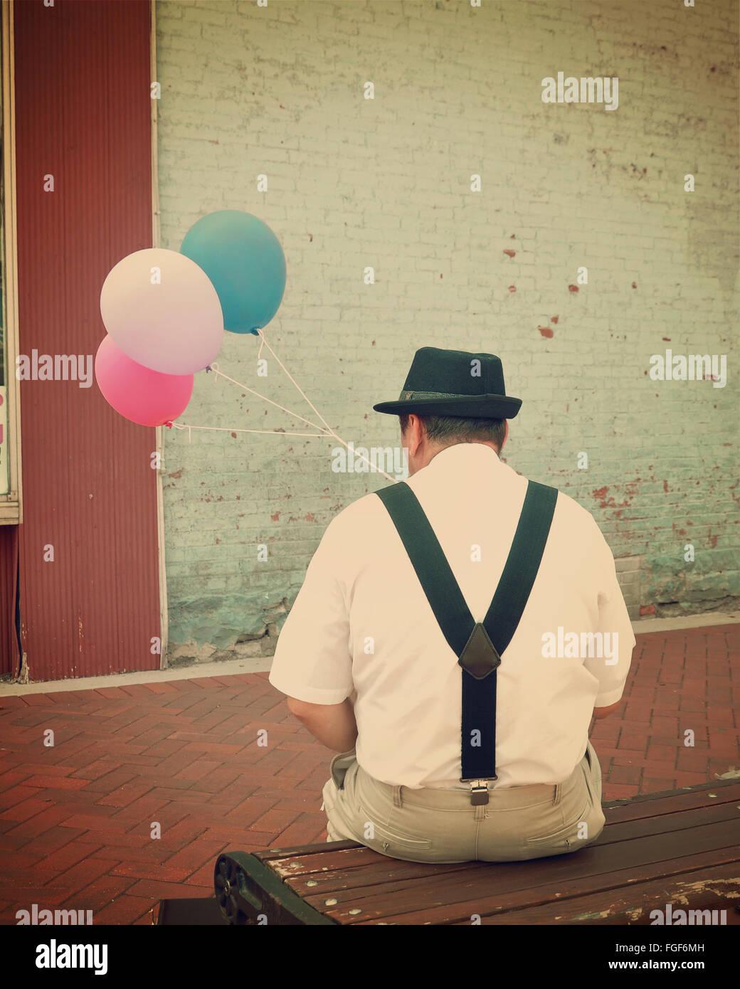 Vintage retro Business-Mann sitzt auf einer Bank Innenstadt mit bunten Luftballons für ein Glück oder Stockbild