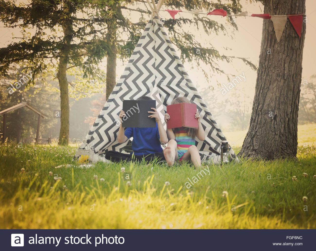 Zwei kleine Kinder lesen Bücher zusammen außerhalb in einem Tipi-Zelt für eine Ausbildung oder Lernkonzept. Stockbild