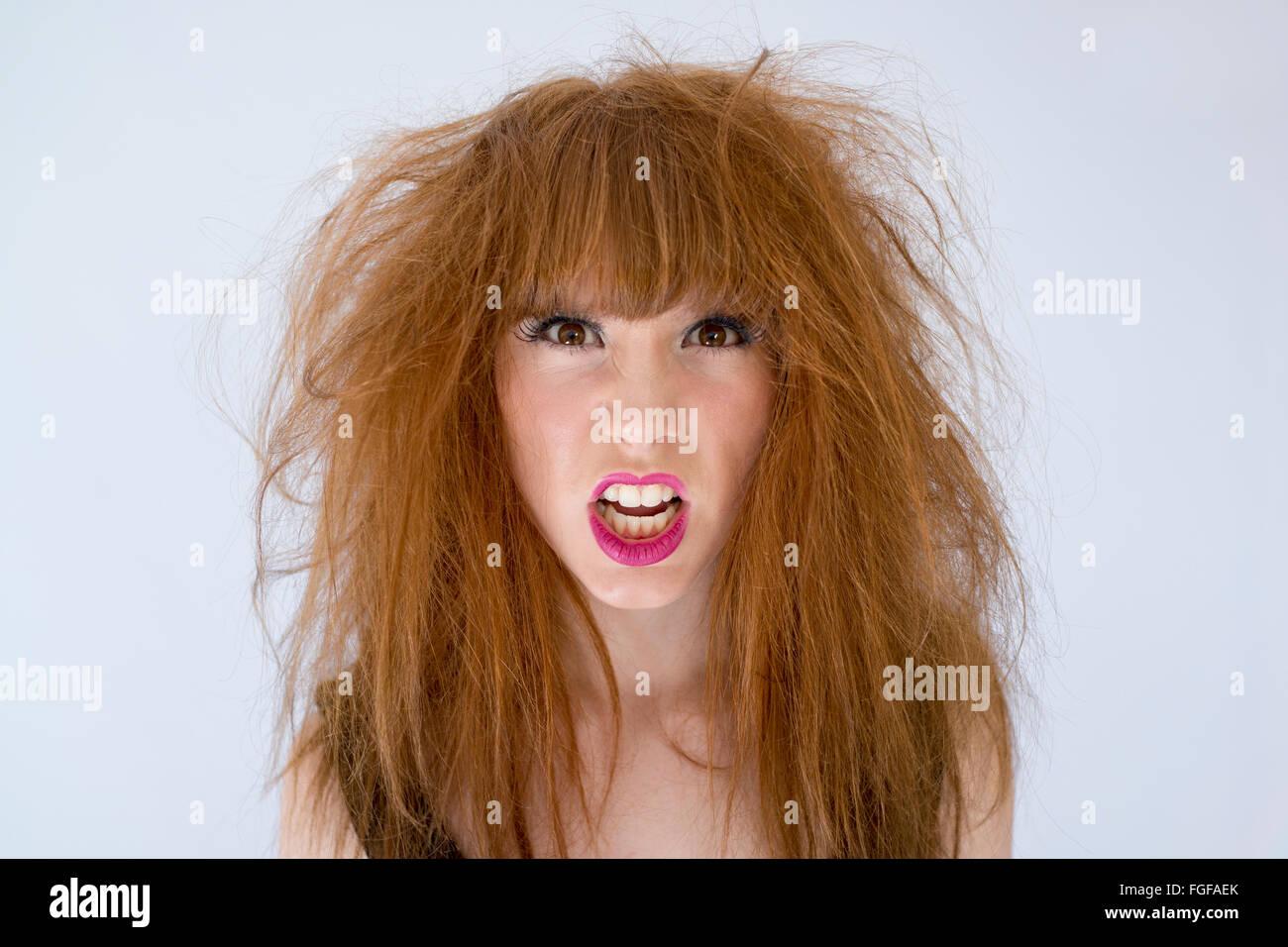 Porträt einer Frau mit chaotisch zerzausten Haaren mit und Ausdruck von Wut Stockbild