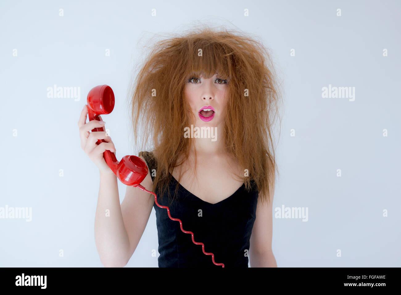 Frau mit strubbeligem Haar hält ein rotes Retro-Telefon mit einem Ausdruck der Verwirrung Stockbild
