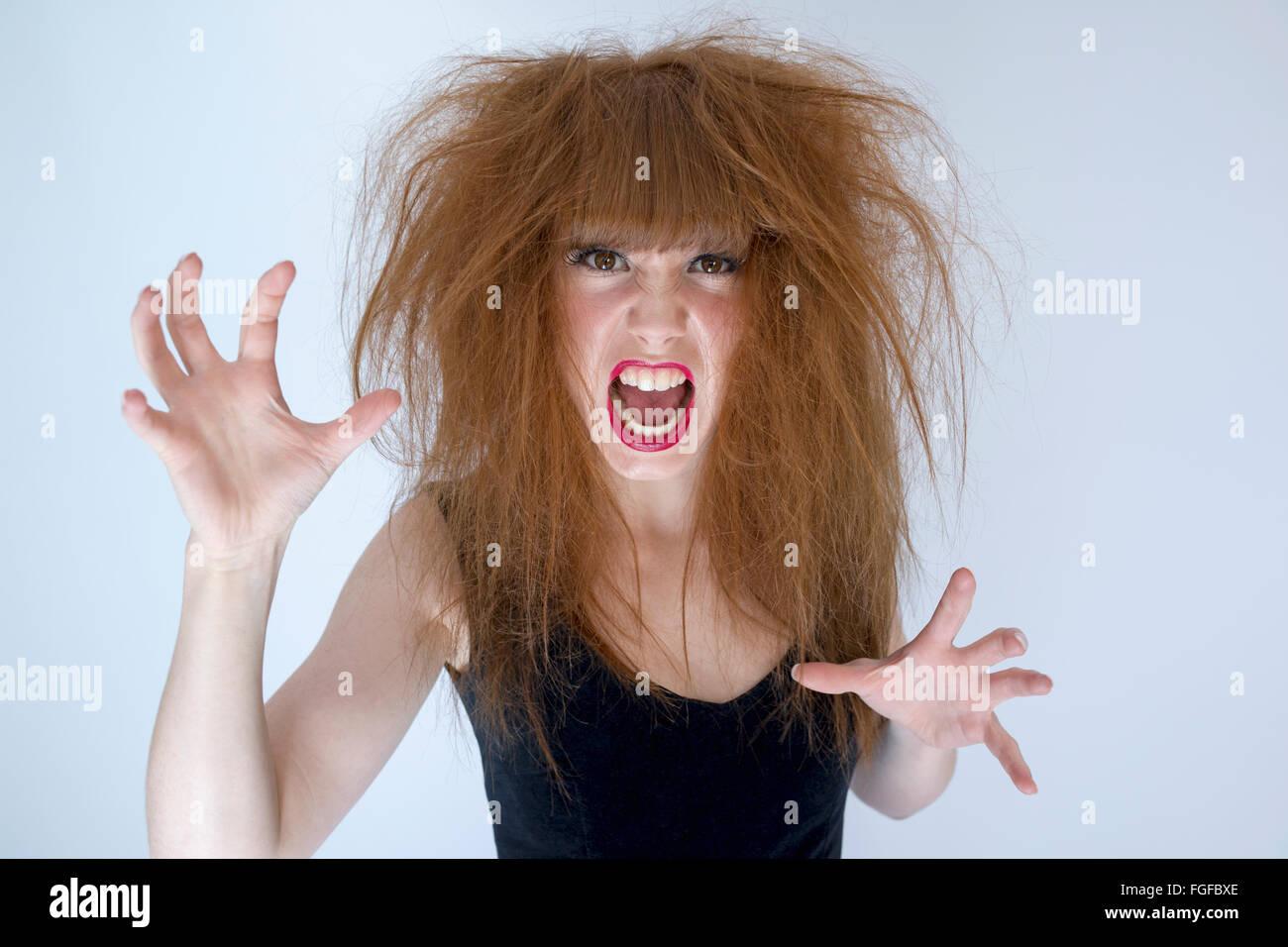 Frau mit chaotischen Wirren langen braunen Haaren zu kämpfen, schreien Stockbild