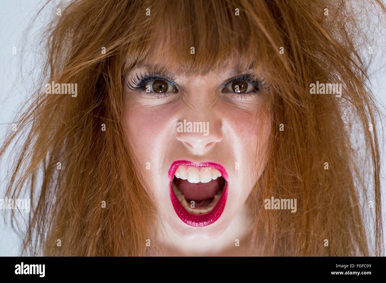 Porträt einer Frau mit chaotisch zerzausten Haaren mit einem Ausdruck von Wut Stockbild