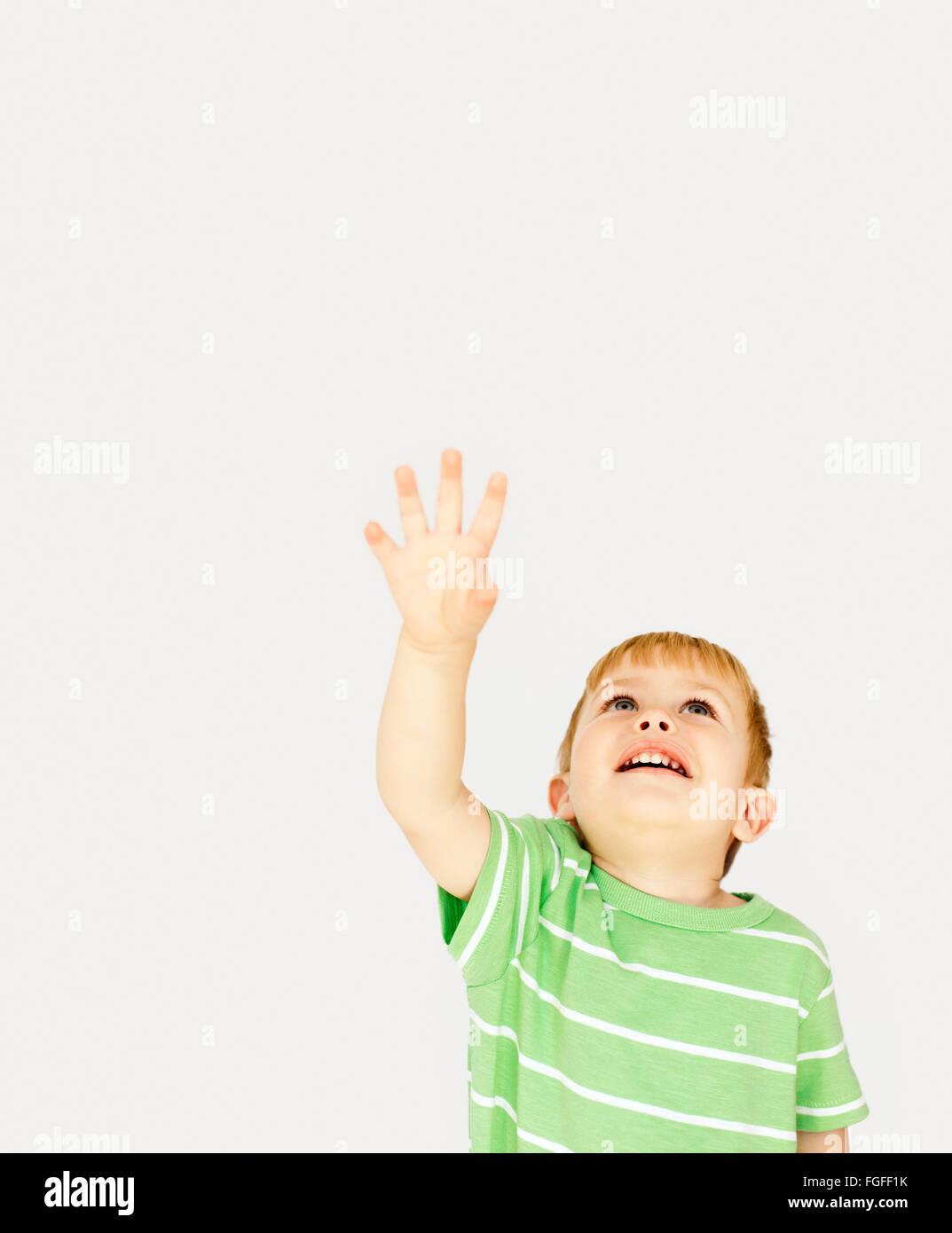 Junge seine Hand in den Himmel zu erreichen Stockbild