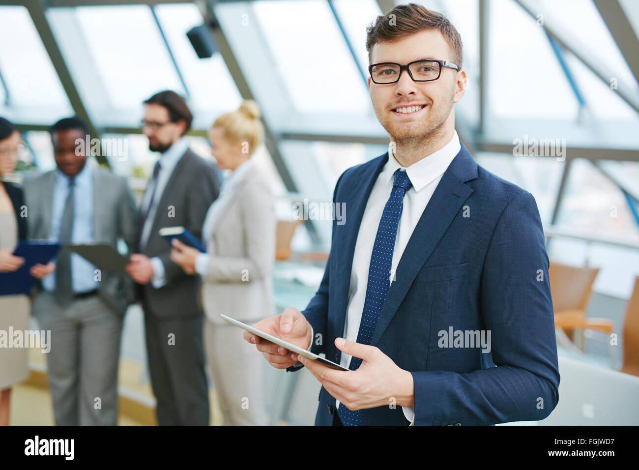 Junge Führungskraft mit Blick in die Kamera auf Grund der arbeitenden Bevölkerung touchpad Stockbild
