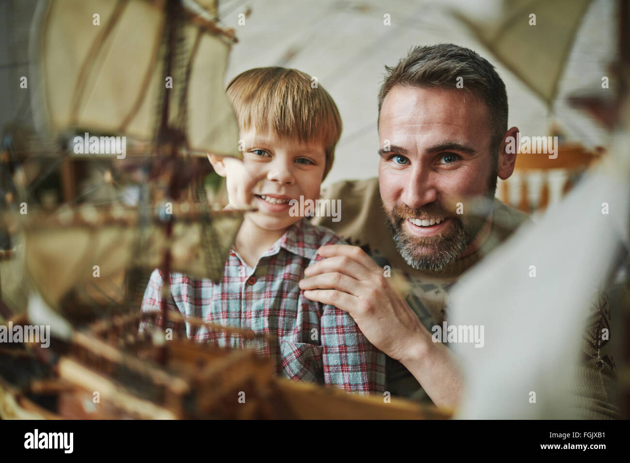 Kleiner Junge und sein Vater, der Blick in die Kamera mit einem Lächeln Stockbild