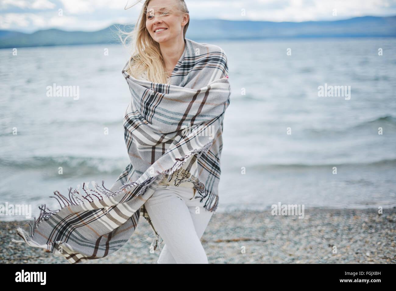 Junge Frau eingewickelt in Plaid zu Fuß am Strand Stockbild