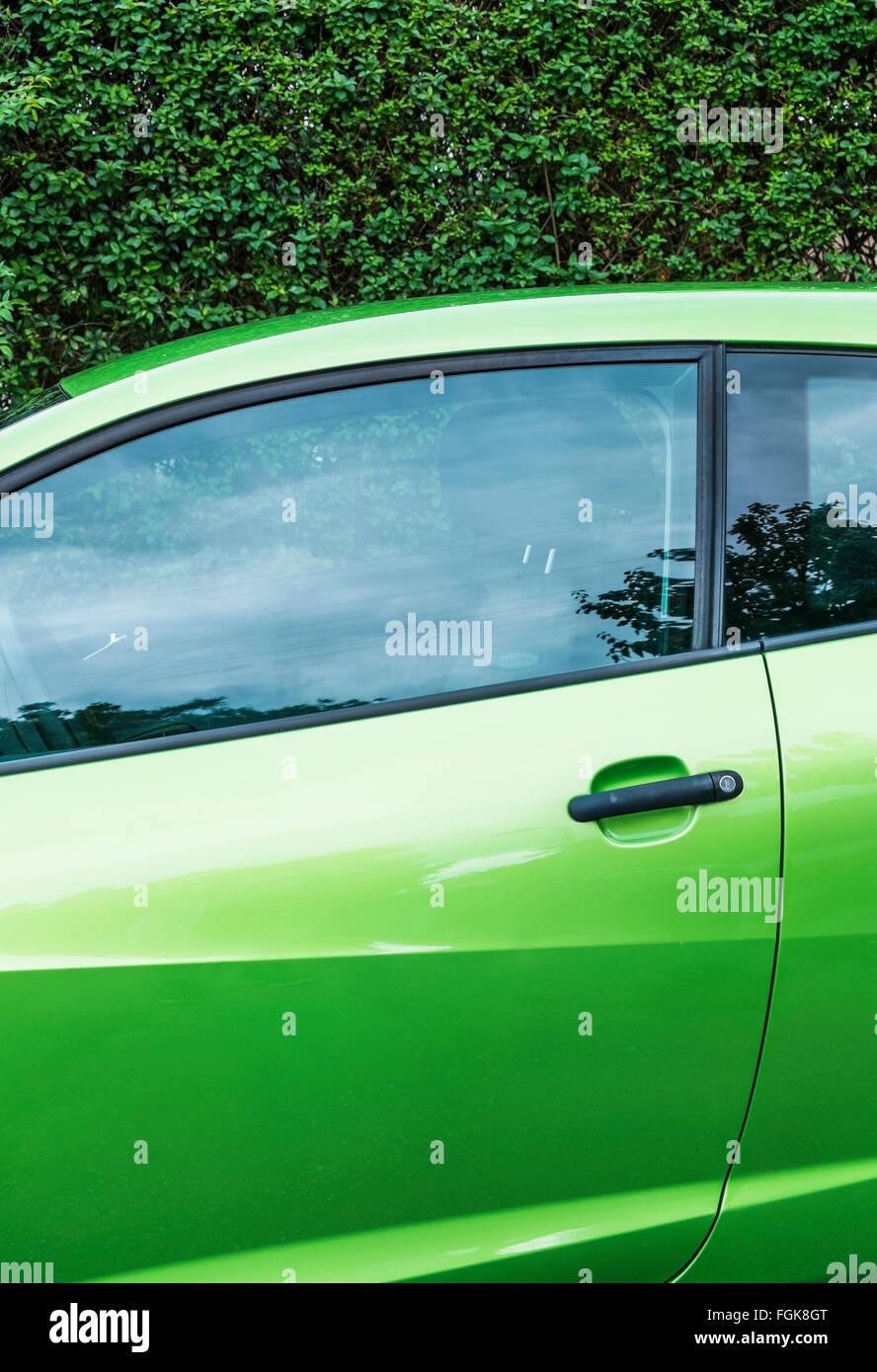 grünes Auto gegen dunkle grüne Hecke Stockbild