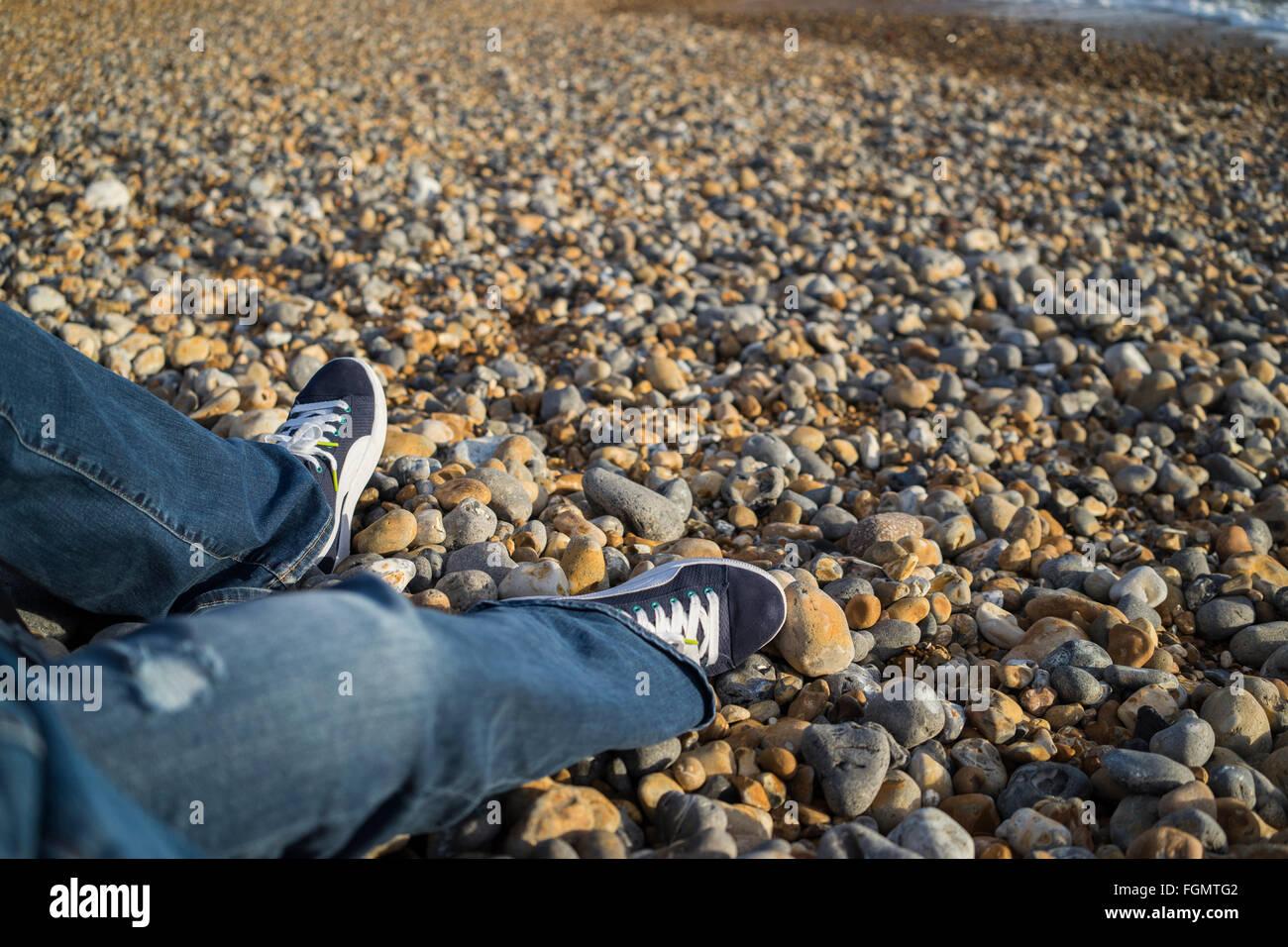 Beine einer Frau in Jeans sitzen am Strand von Brighton, UK Stockfoto
