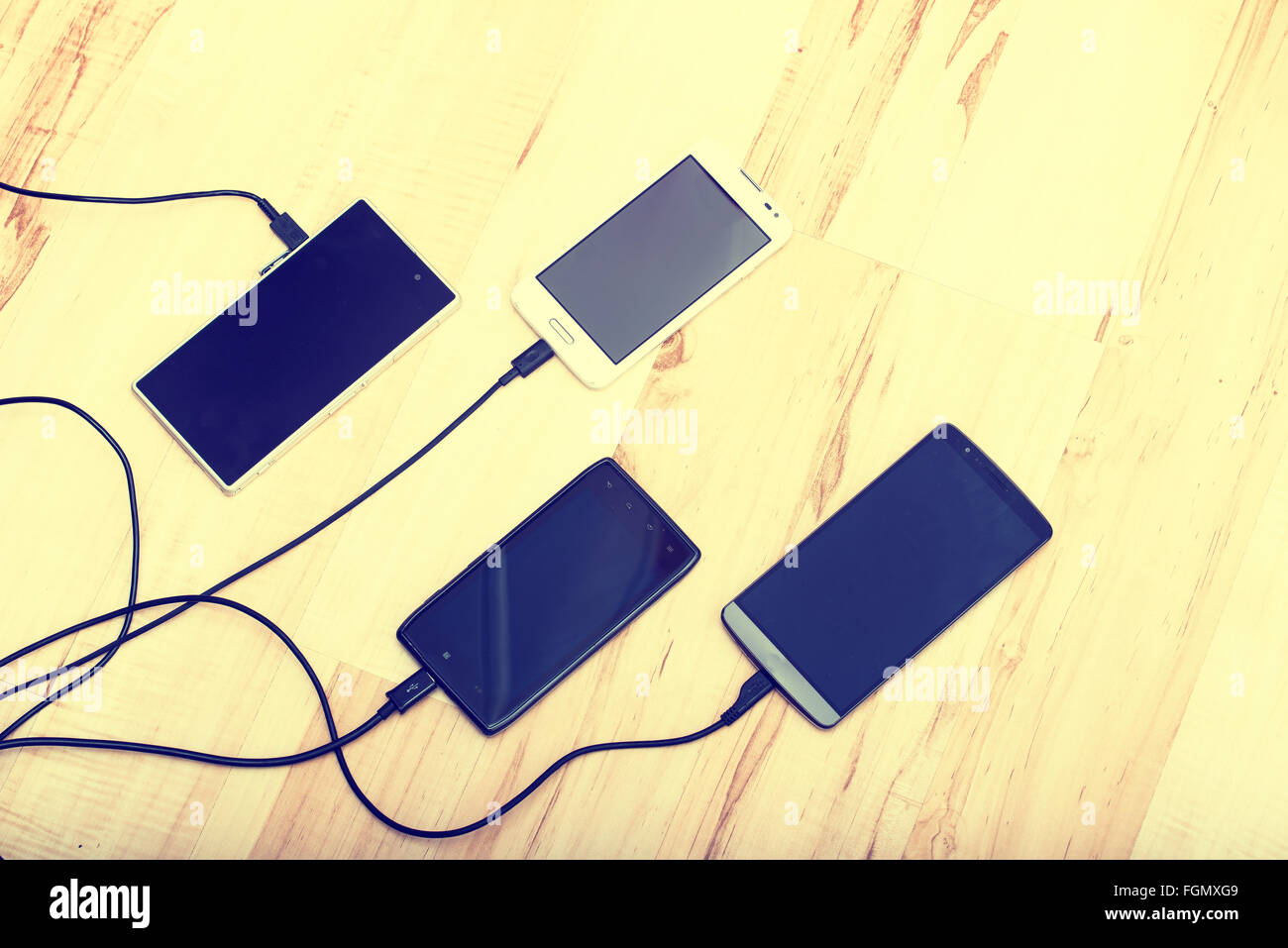 vier Smartphones verbunden mit Ladegeräten Stockbild