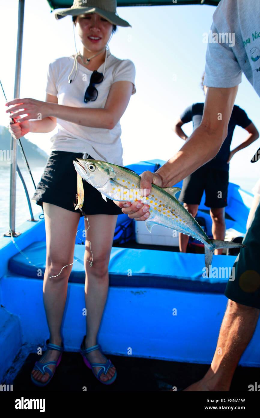 Eine asiatische weibliche Touristen mit einem frischen Fang der spanische Makrele Stockbild