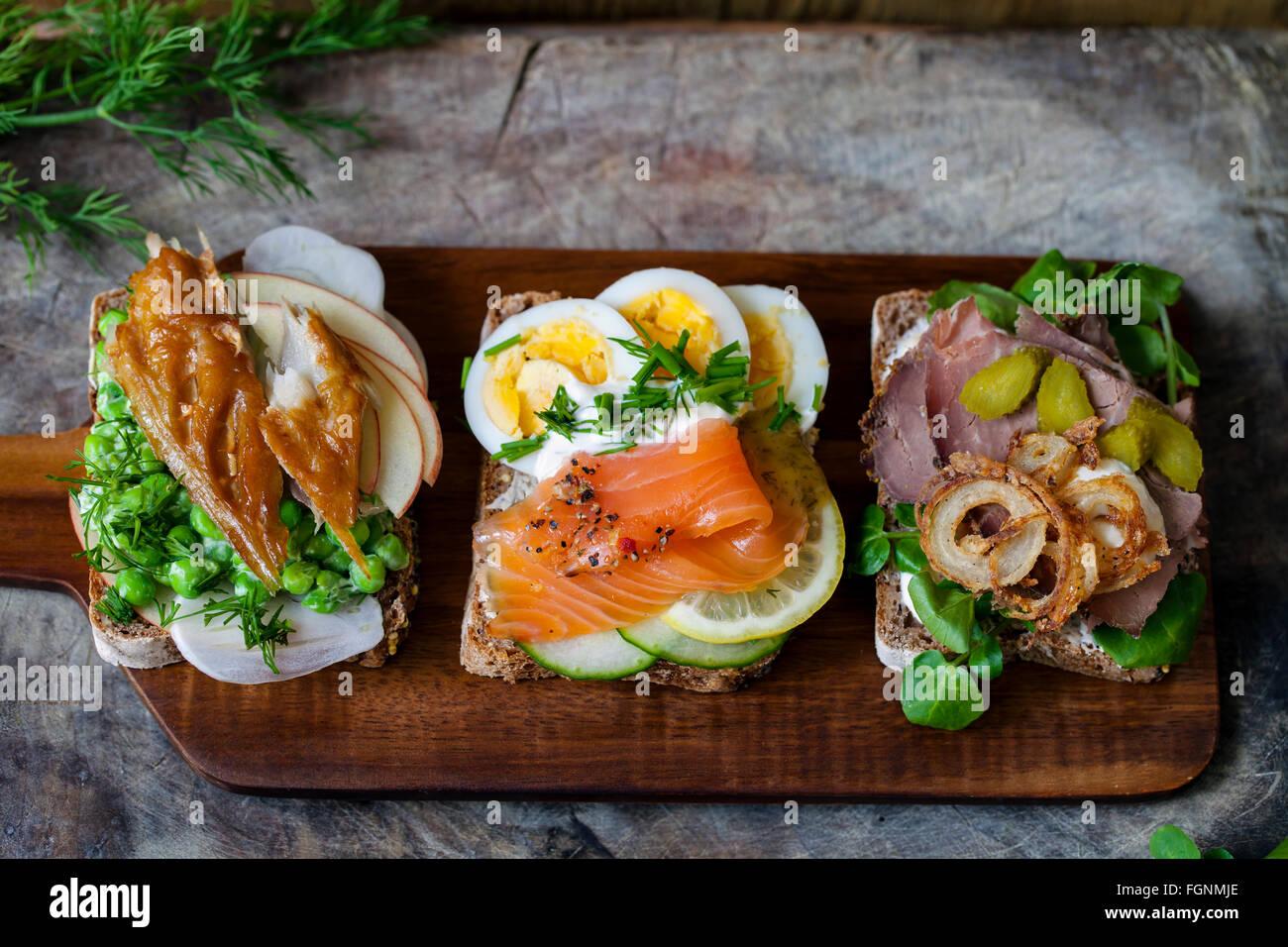 Skandinavische belegte Brötchen mit geräucherter Makrele, Lachs und Ei und Roastbeef und knusprigen Zwiebeln Stockbild