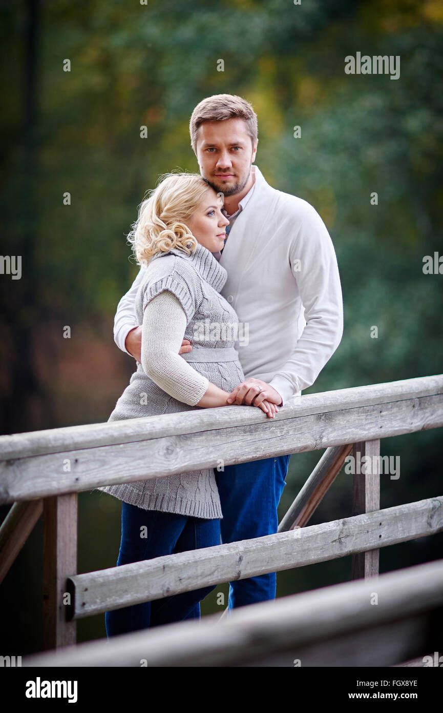 Junge, blonde Frau mit ihrem Ehemann im Park auf der Brücke Stockbild