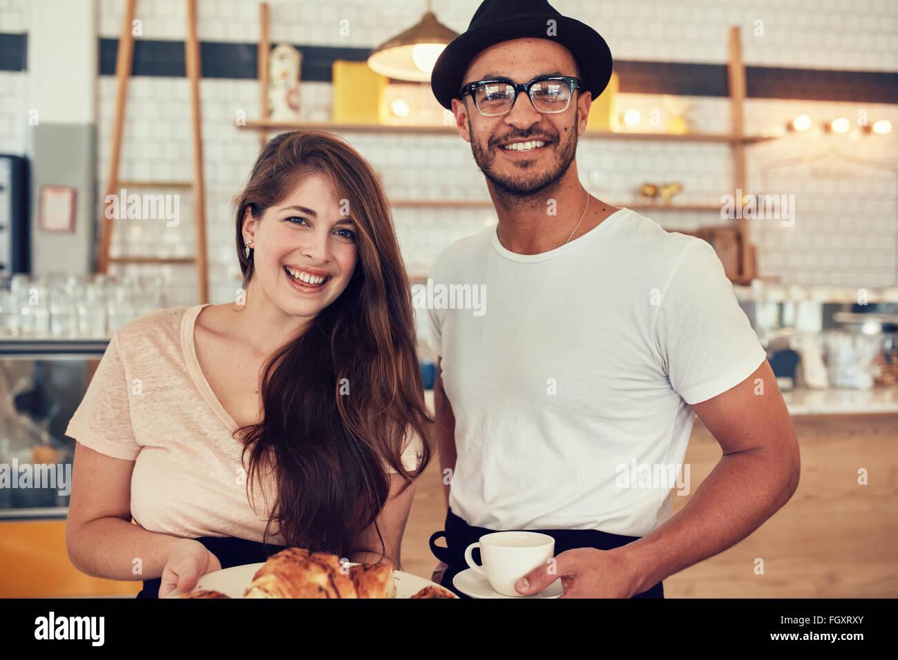 Porträt von glücklicher junger Mann und Frau, die ihr Mittagessen in einem Café, Blick in die Kamera Stockbild
