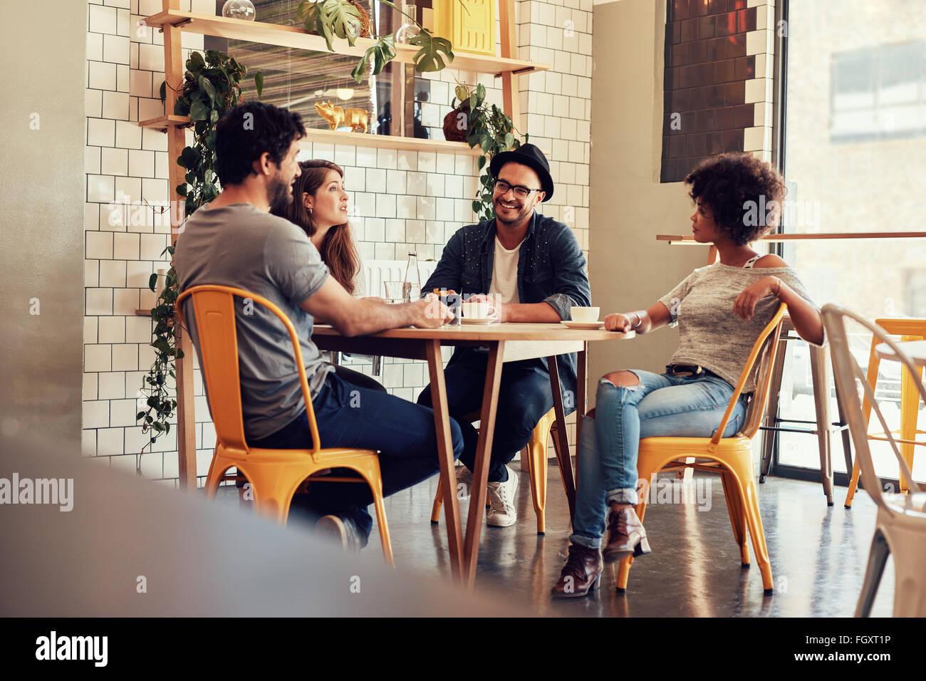 Junge Menschen an einem Cafétisch sitzen. Gruppe von Freunden in einem Café im Gespräch. Stockbild