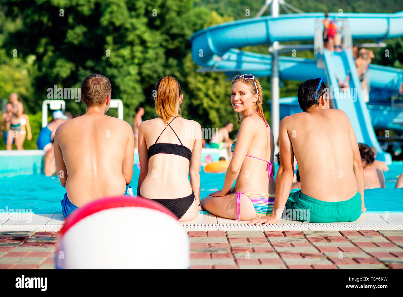 Zwei Paare, Sonnenbaden am Pool. Hitze des Sommers. Stockbild
