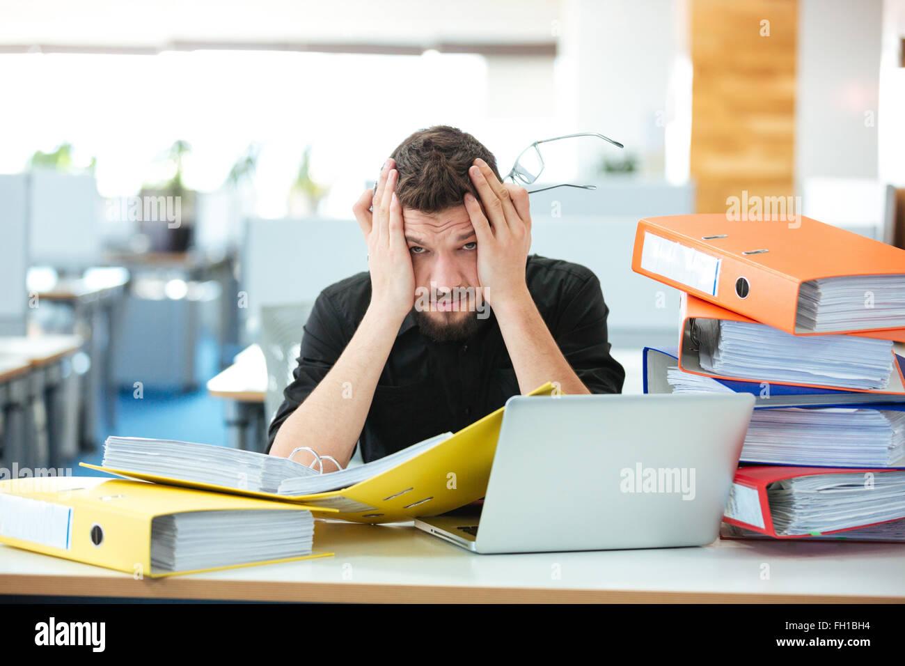 Müde Geschäftsmann mit Papieren im Büro arbeiten Stockbild