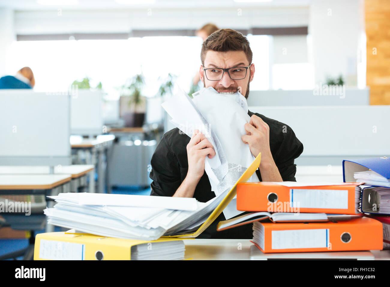 Junger Geschäftsmann beißen Papier im Büro Stockbild