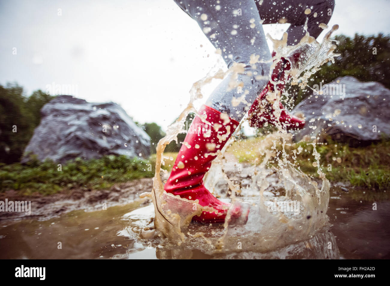 Frau im schlammigen Pfützen plantschen Stockbild