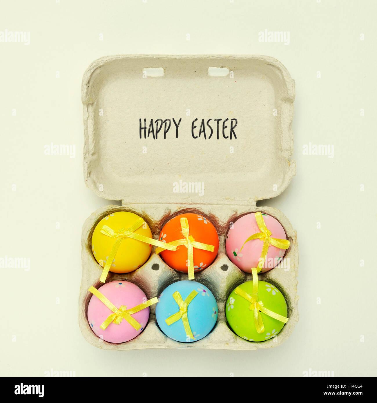 High-Angle Shot von einem Eierkarton voller dekorierte Ostereier in verschiedenen Farben und den Text Frohe Ostern Stockbild