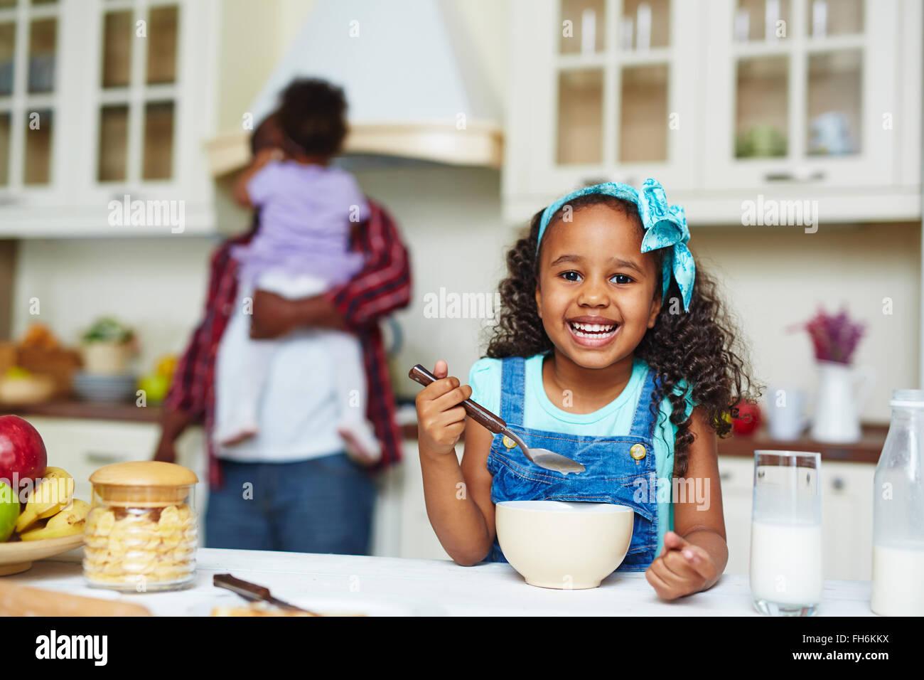 Fröhliches afroamerikanische Mädchen Essen morgens cornflakes Stockbild