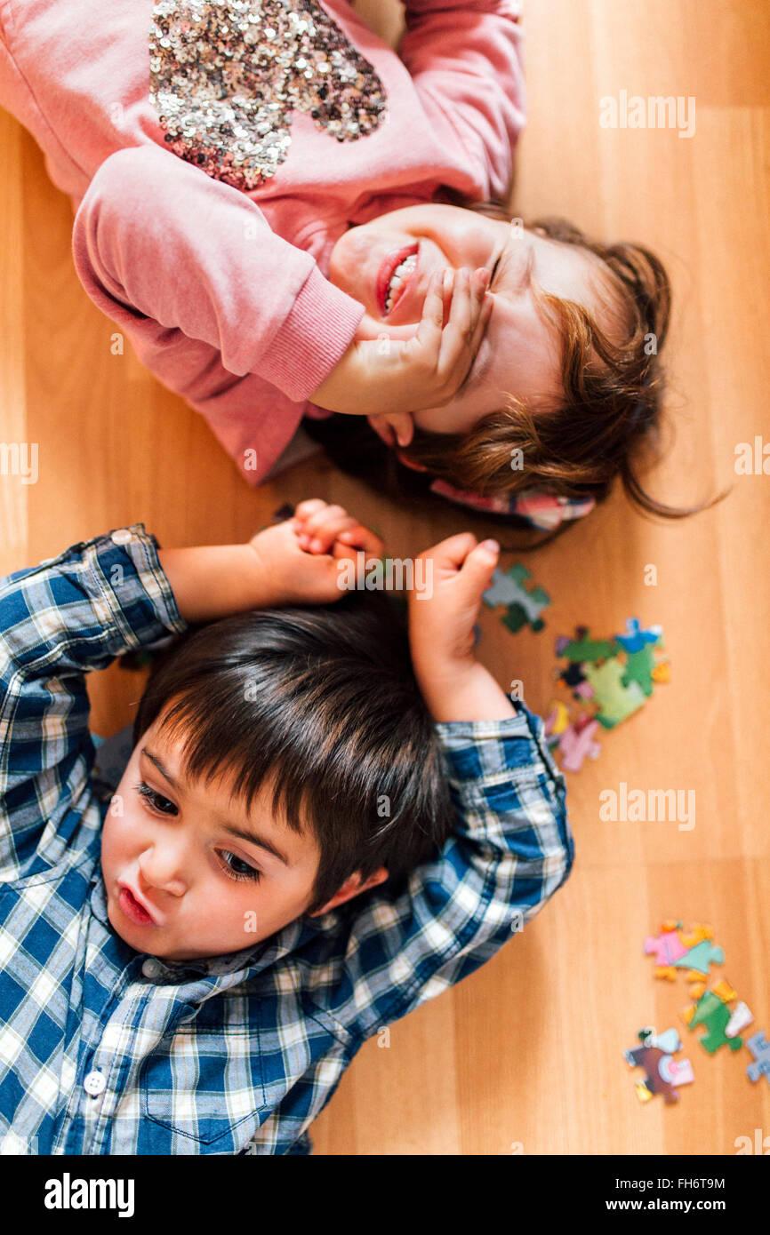 Jungen und Mädchen auf dem Boden liegend Stockbild