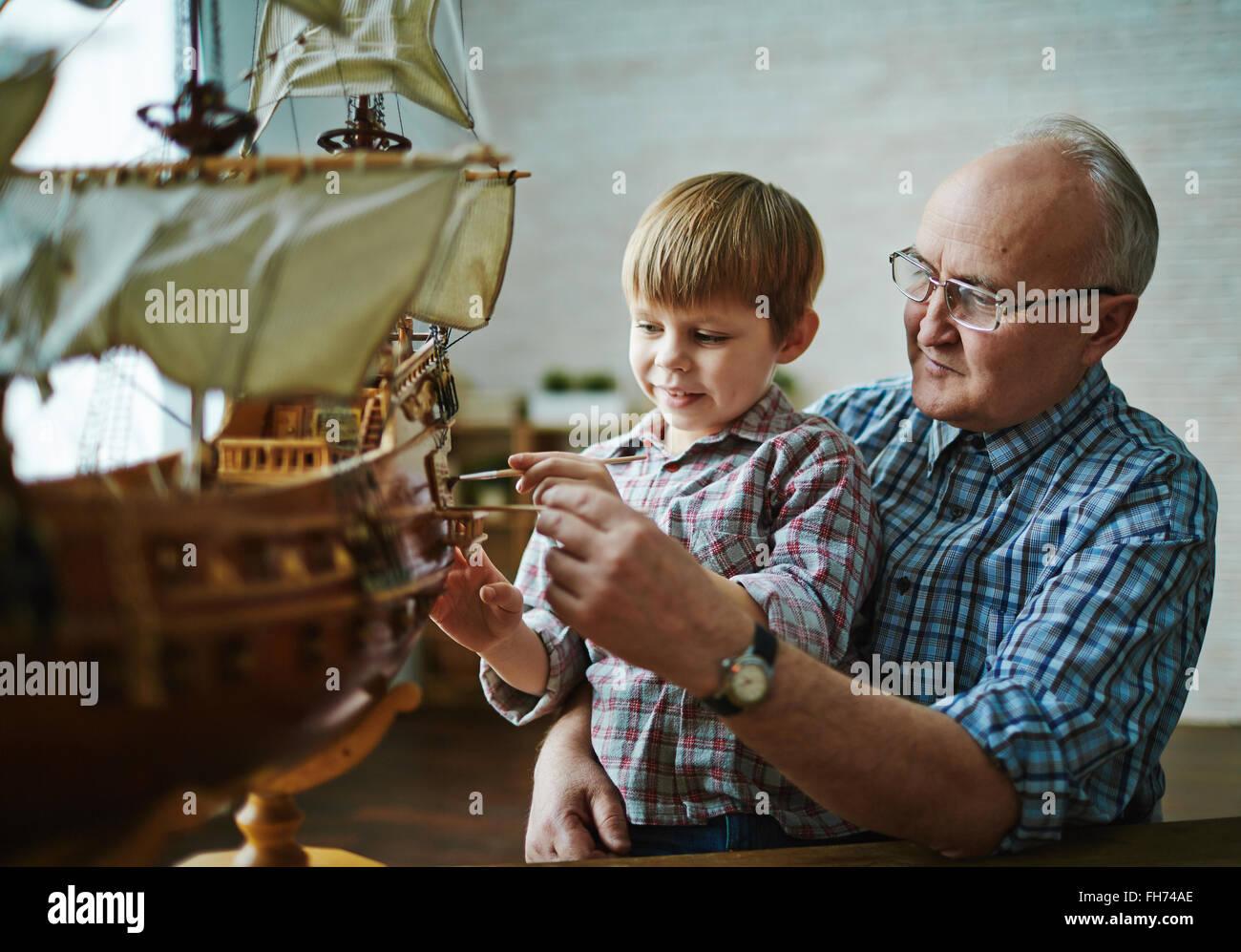 Kleiner Junge Malerei Spielzeug Schiff mit Hilfe der Großvater Stockfoto