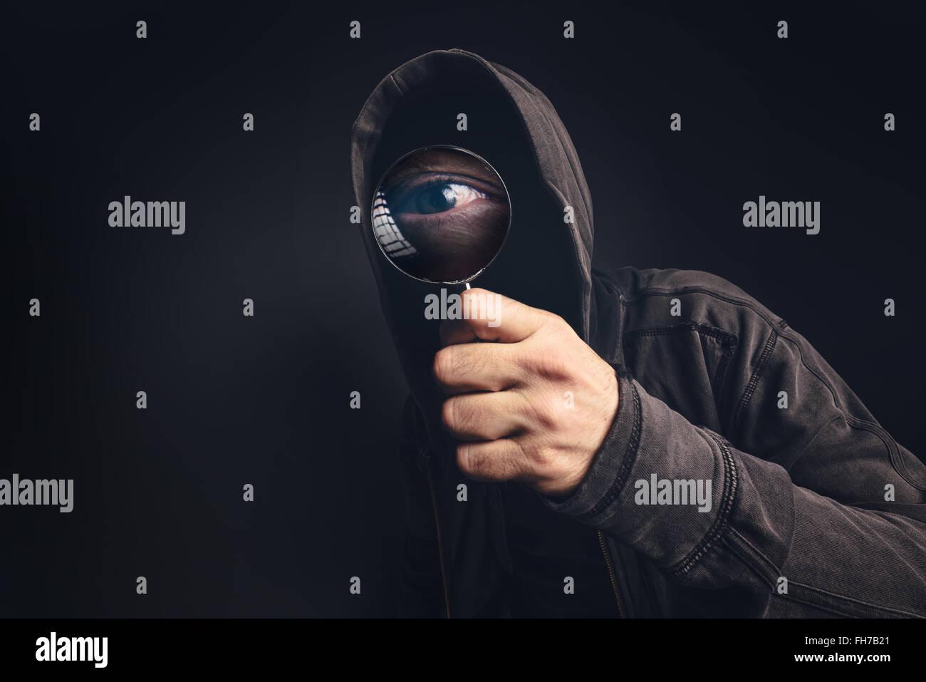 Bizarre Kapuzen gruselige Person mit Lupe, Fokus auf vergrößerte Augen spähen Sie Stockbild