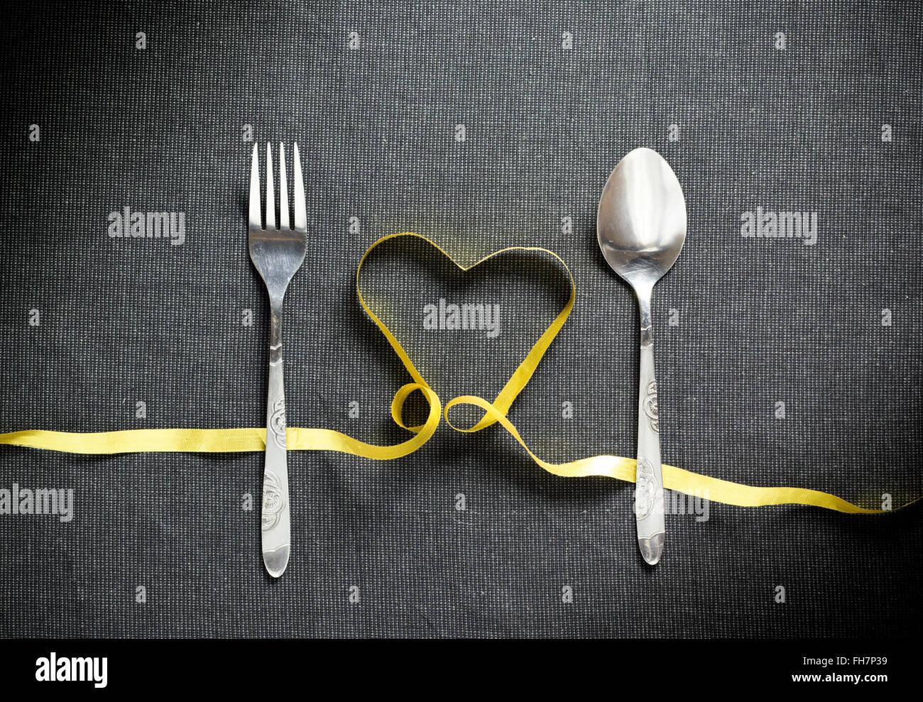 Gabel und Löffel mit Herzform aus gelbem Band auf Schwarz strukturierten Hintergrund Stockbild