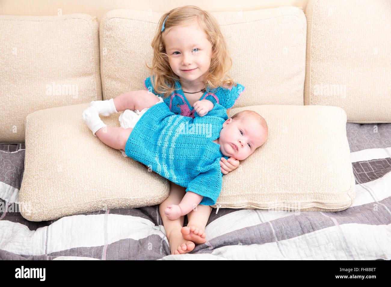 03ab966e66714 Zwei Schwestern. Ältere Schwester Kind umarmt sein neugeborenes  Schwesterchen. Süße Kinder Mädchen auf Bett zu Hause.