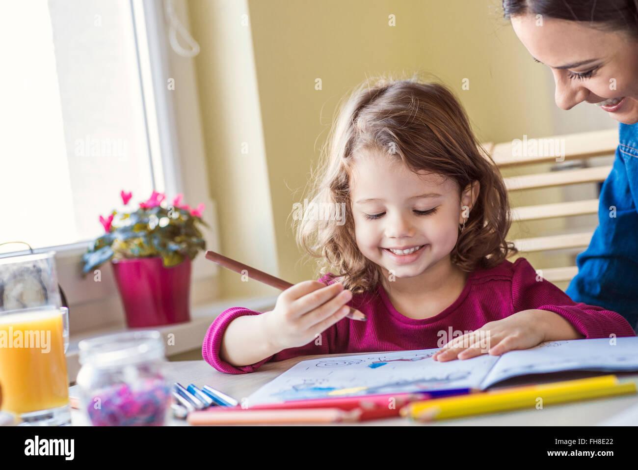 Porträt der lächelnde Mädchen malen mit Buntstiften Stockbild