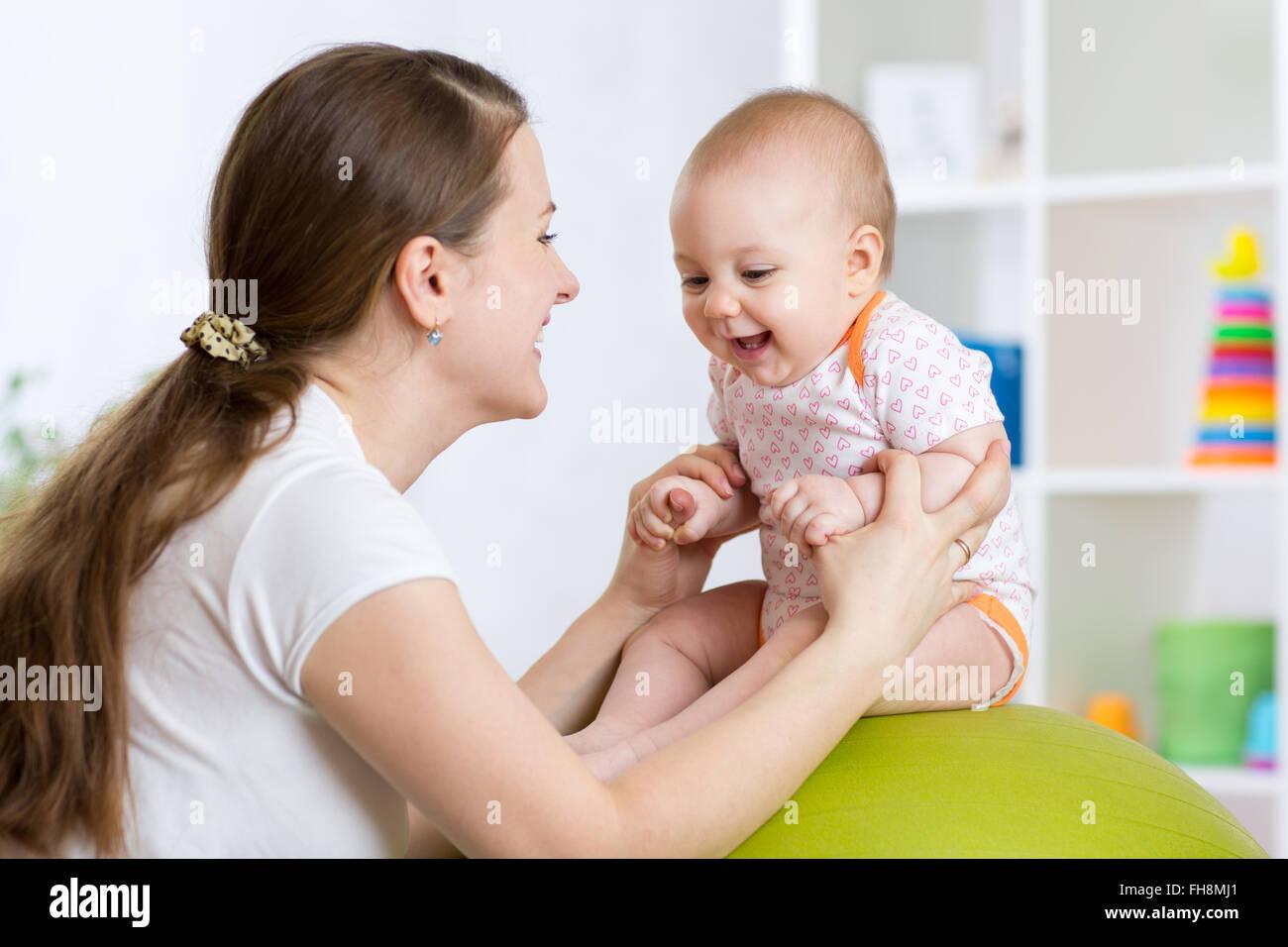 Glückliche Mutter mit Kind Übungen mit grünen