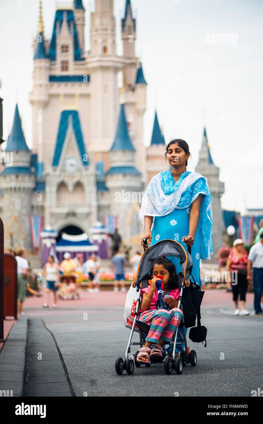 Verschiedenen Kulturen Menschen, die Spaß mit der Familie vor der Hauptburg im Vergnügungspark von Disney Stockbild