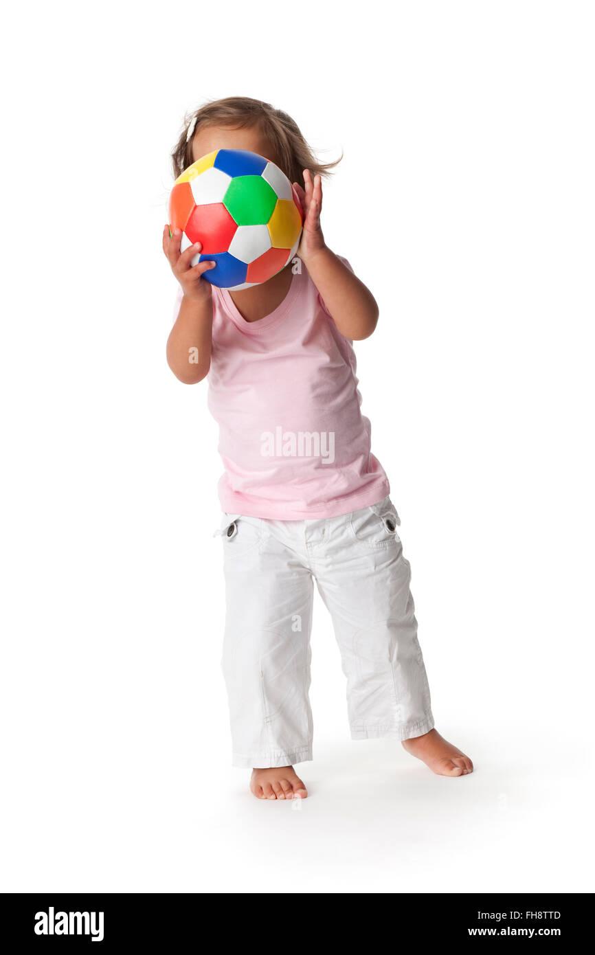 Kleinkind Mädchen versteckt sich hinter eine farbige Kugel auf weißem Hintergrund Stockbild