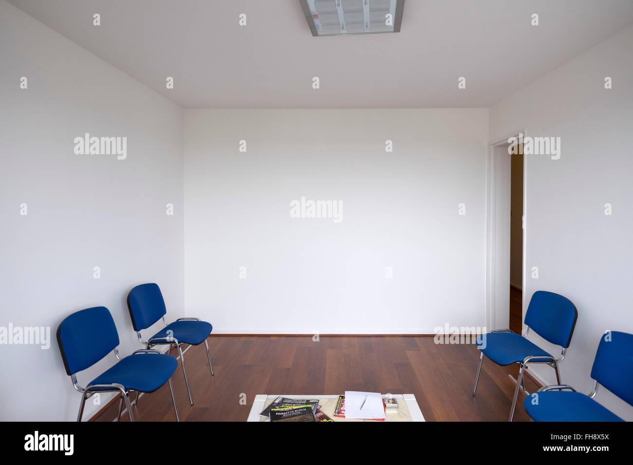 Leere Arzt-Wartezimmer mit weißen Wänden und blauen Stühlen Stockfoto
