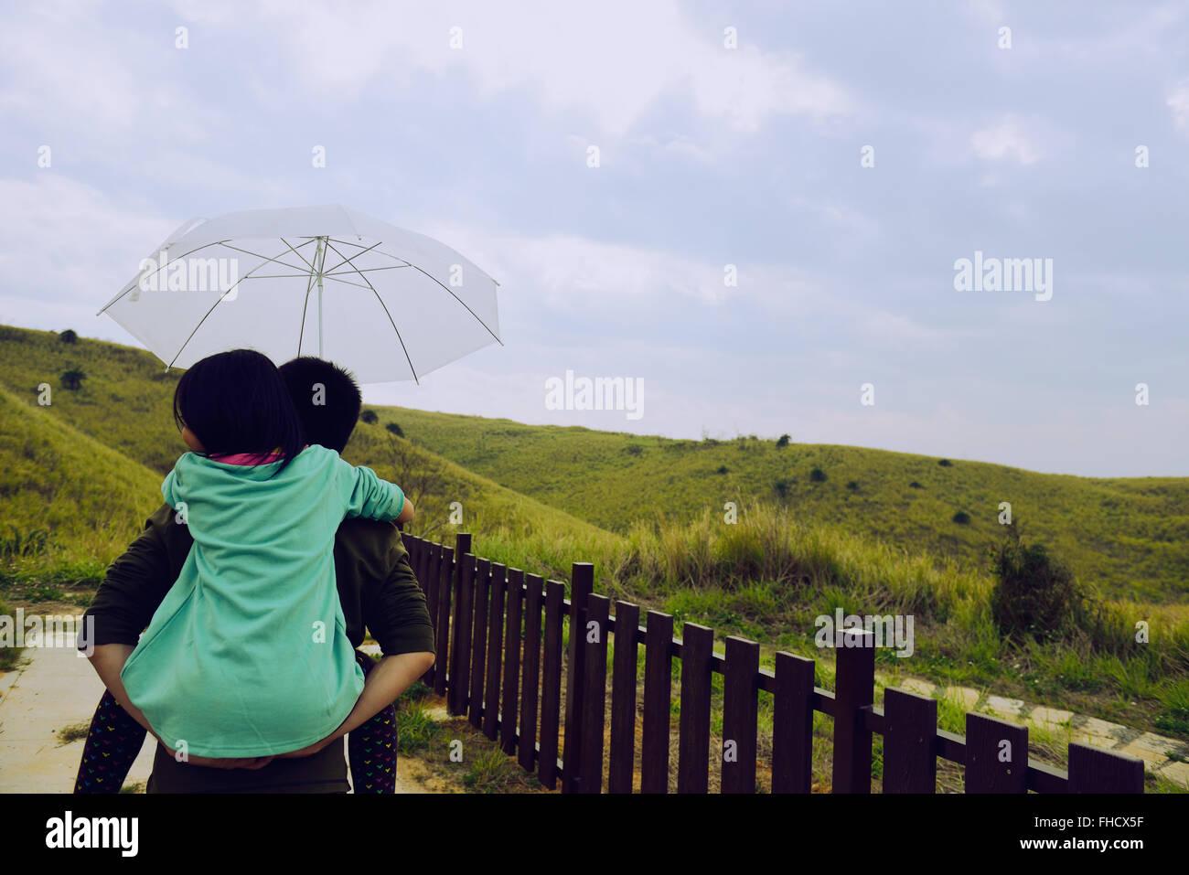 Tochter auf Vaters Rücken nehmen Regenschirm, Mädchen auf Vaters Rücken nehmen Regenschirm, Vater Stockbild