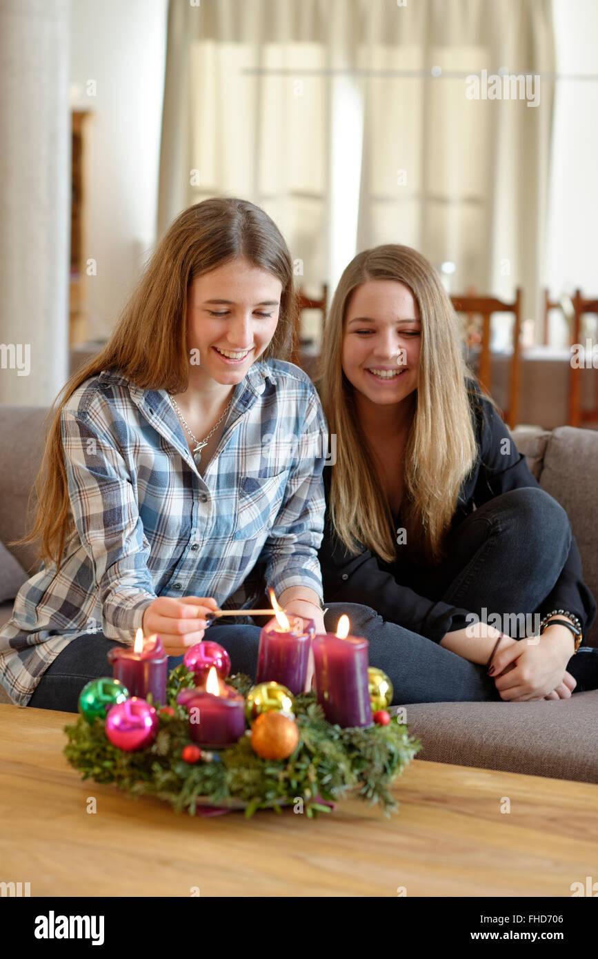 Junge Frau Beleuchtung Kerze am Adventskranz, während ihr Freund gerade ist Stockfoto