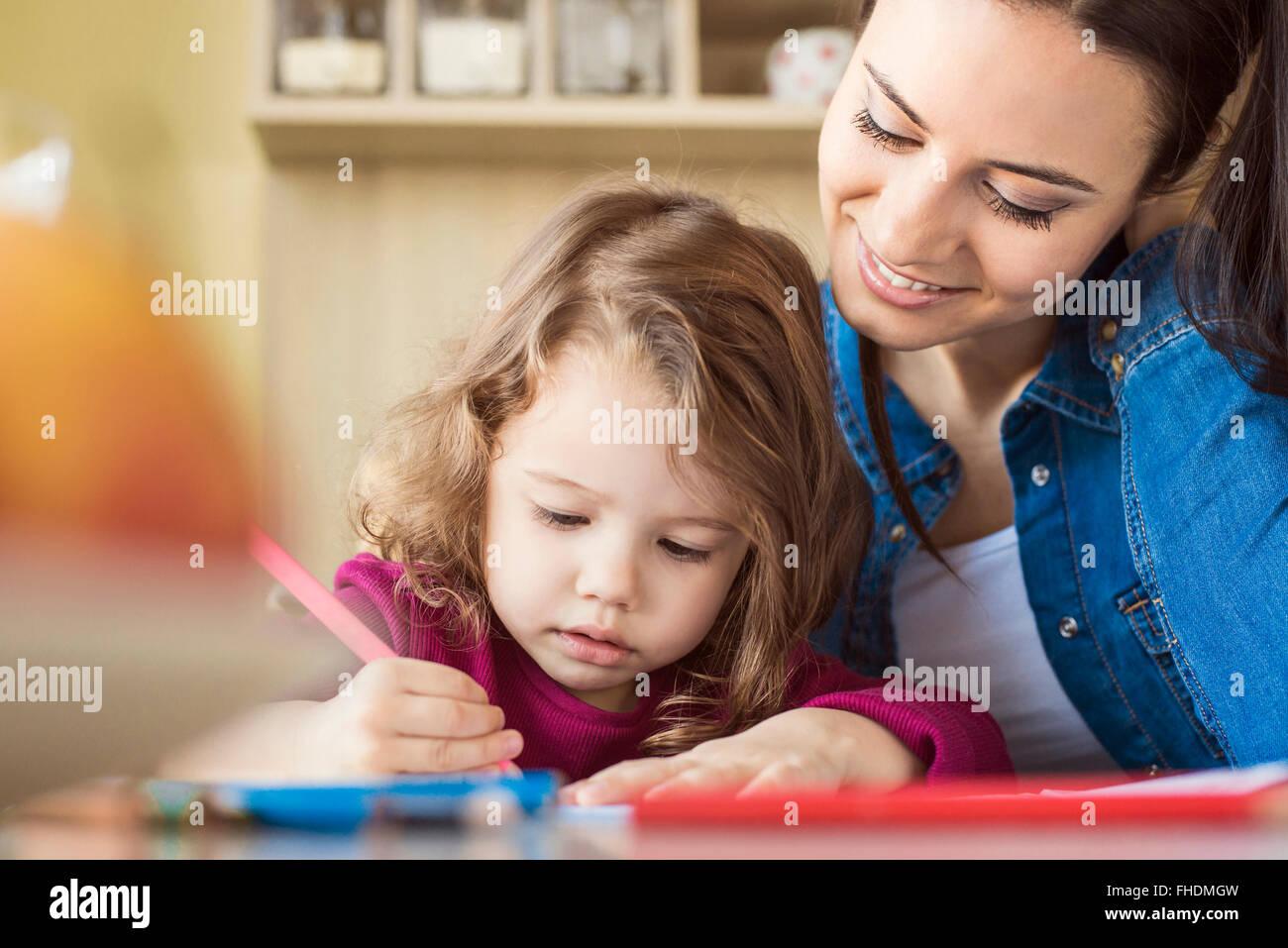 Porträt von kleinen Mädchen malen mit Farbstiften, während Mutter ihr zusieht Stockbild