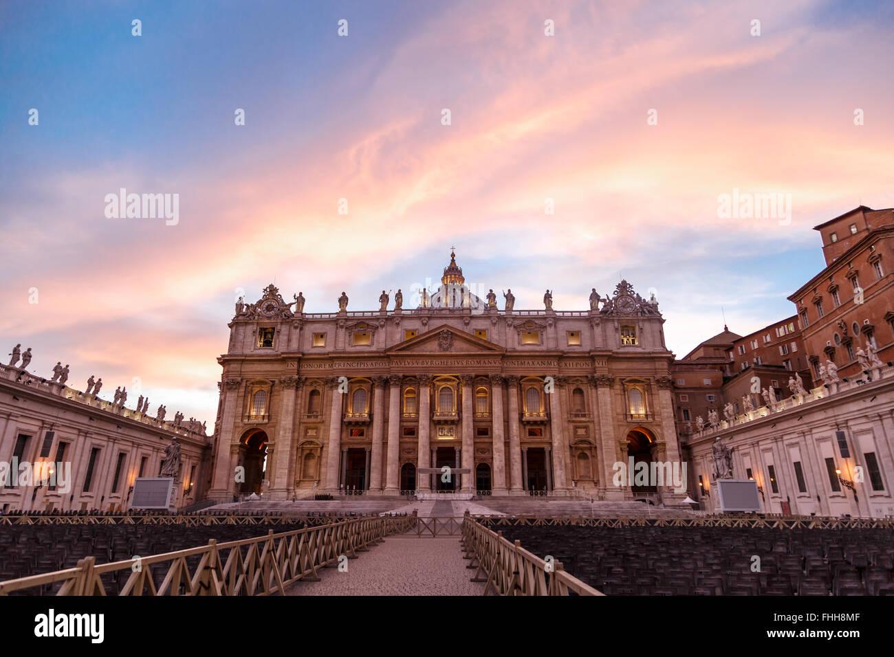 Vorderansicht von der Basilika St. Peter im Vatikan mit Mitmenschen, auf blauen Wolkenhimmel Backgroundat Sonnenuntergangszeit. Stockbild