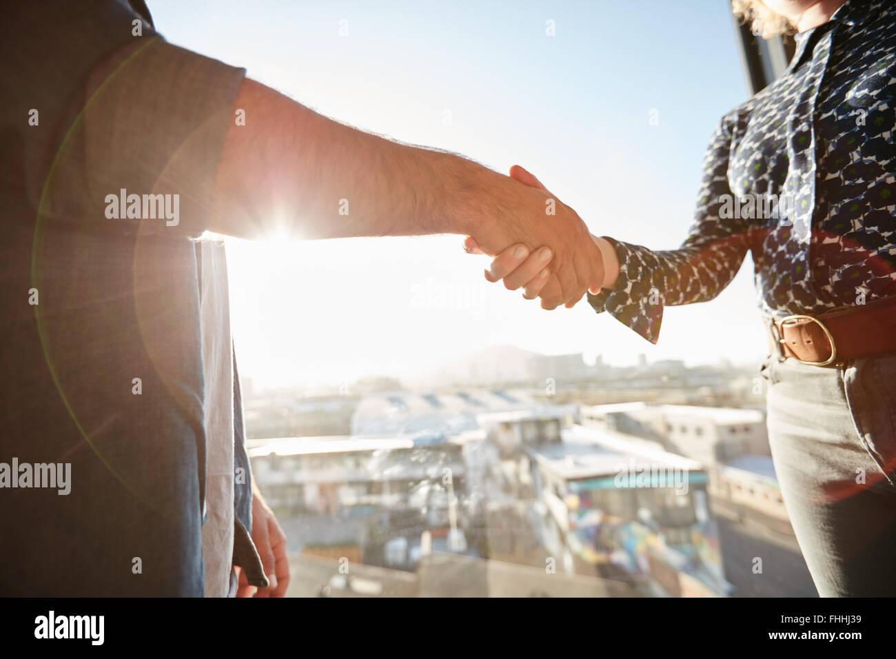 Handschlag von zwei Mitarbeitern mit Sonnenlicht. Männliche Führungskraft seine Hand mit Kollegin, Konzentration Stockbild