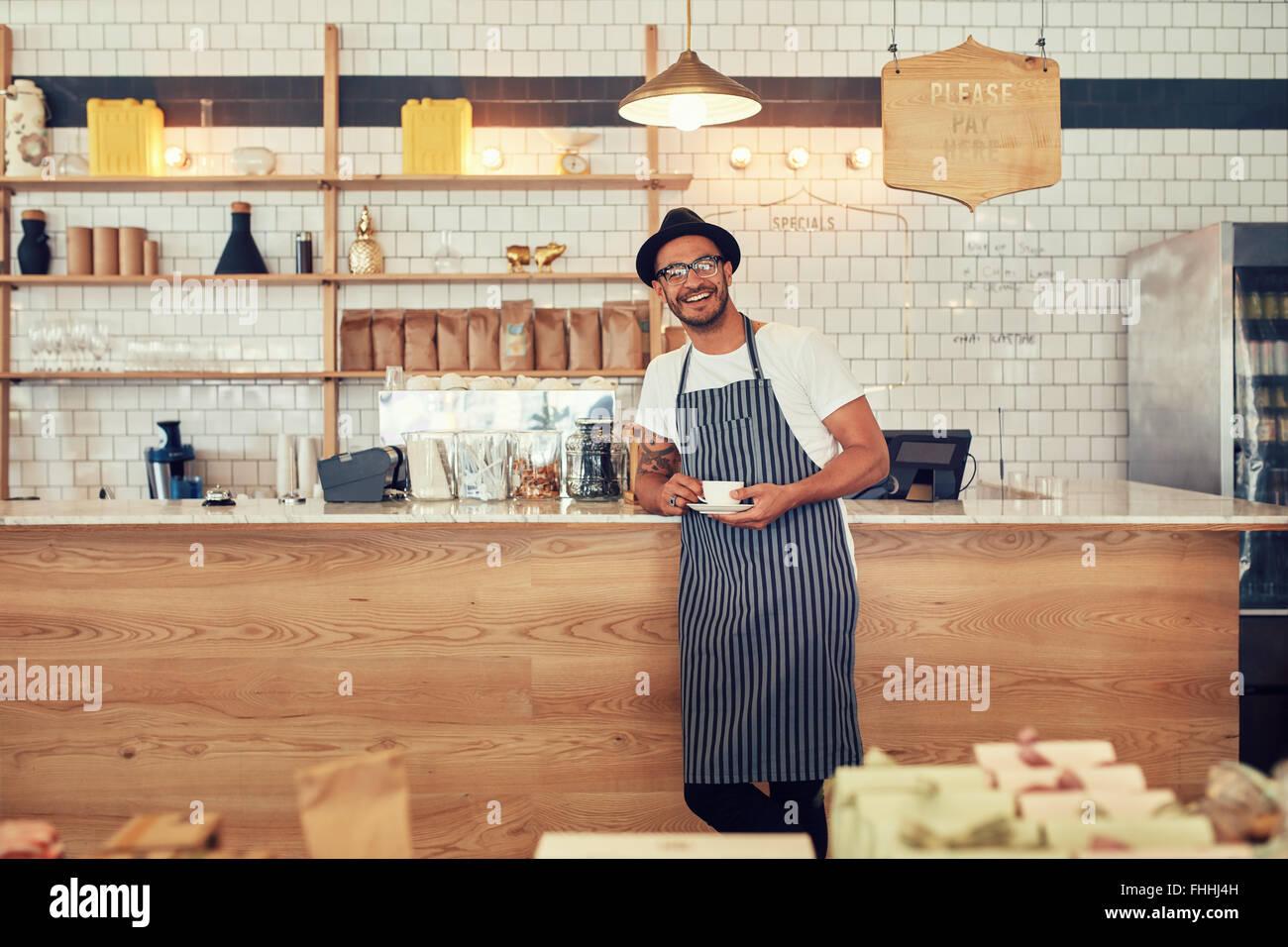 Porträt von glücklicher junger Mann trägt eine Schürze und Mütze stehend an einem Café Schalter hält eine Tasse Stockfoto