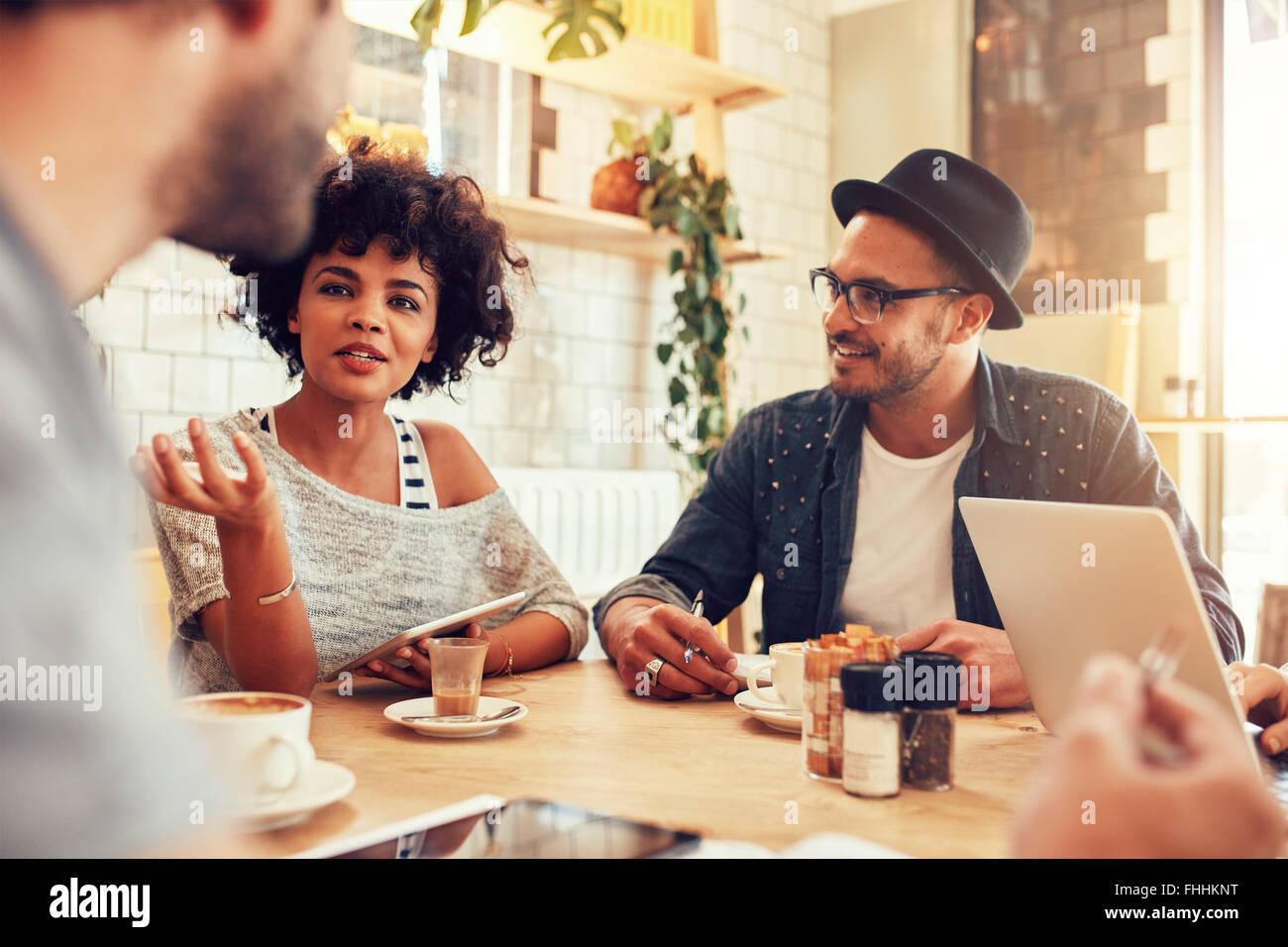 Porträt der jungen Frau im Gespräch mit Freunden in einem Café. Gruppe von Jugendlichen in einem Stockbild
