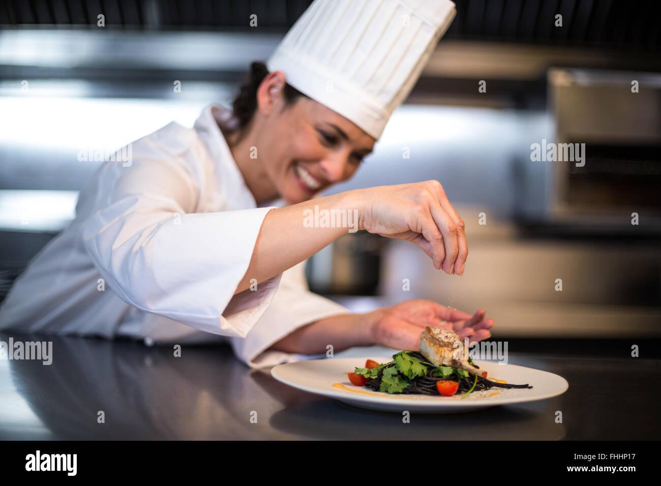 Happy Chef würzen ihren Teller Stockbild