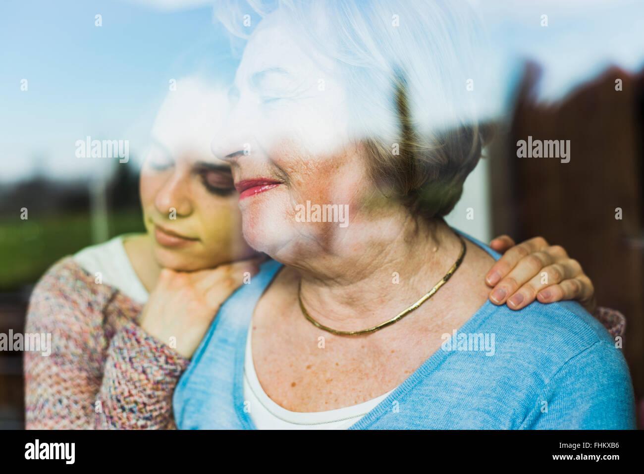 Junge Frau und ältere Frau mit geschlossenen Augen hinter einer Fensterscheibe Stockbild