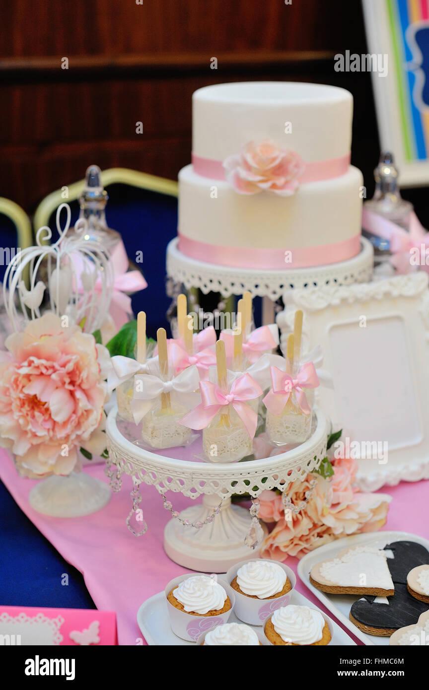Hochzeitstorte Mit Roten Rosen Und Cupcakes Dekoriert Stockfoto