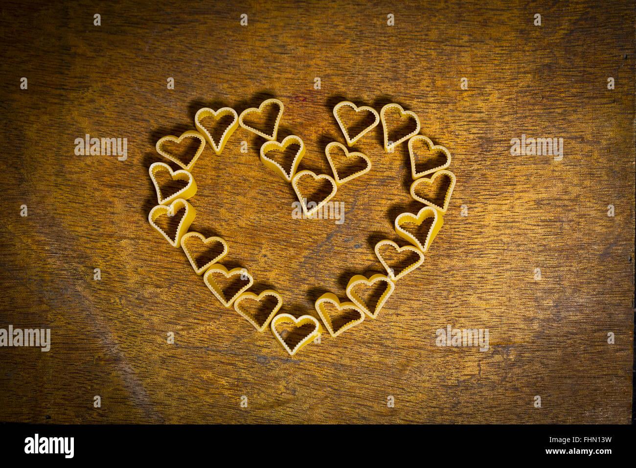 Herzförmige Nudeln bilden ein Herz auf Holz Stockfoto