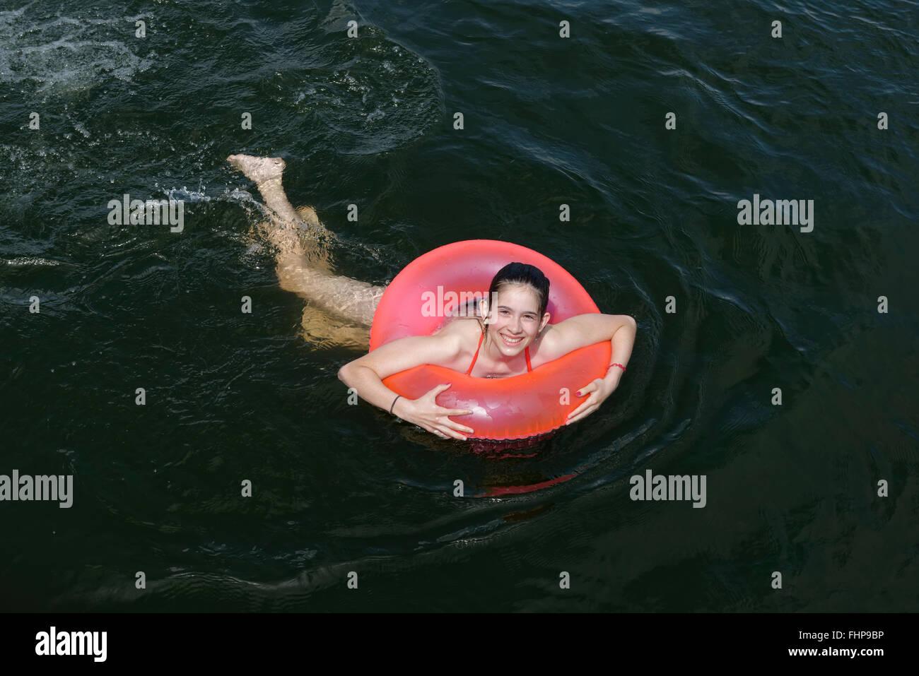 Deutschland, Wustrow, Mädchen Schwimmen mit schwimmenden Reifen im Labussee Stockfoto