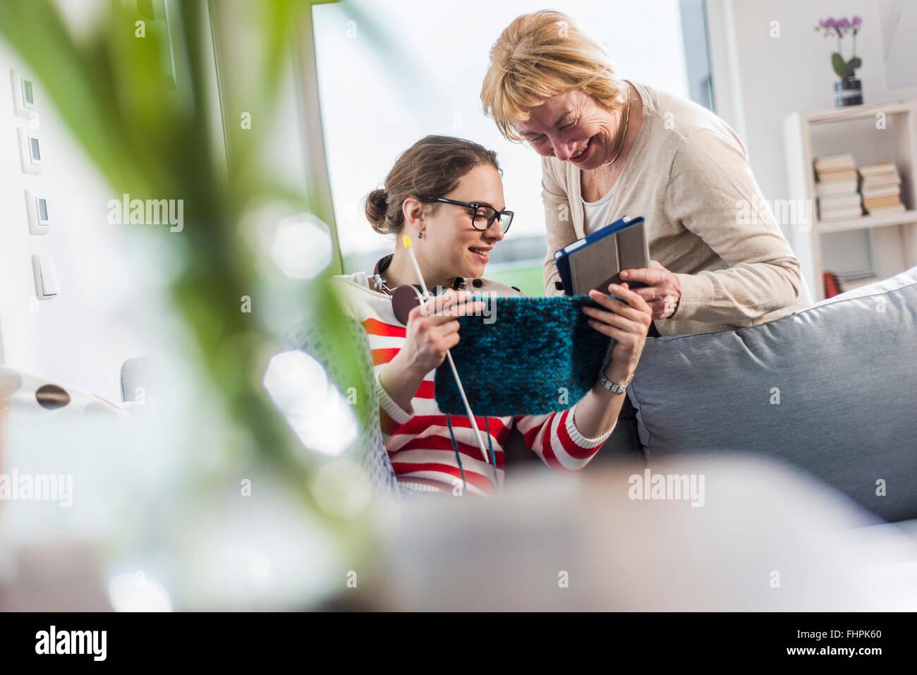 Junge Frau und ältere Frau mit Strick und digital-Tablette auf couch Stockfoto
