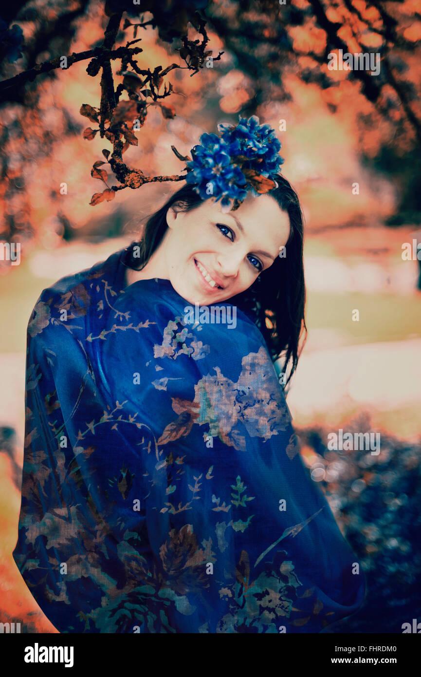 dunkle Haare junge lächelnde Frau posiert im park Stockbild